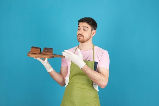 Młody kucharz trzyma świeże plastry ciasto czekoladowe.