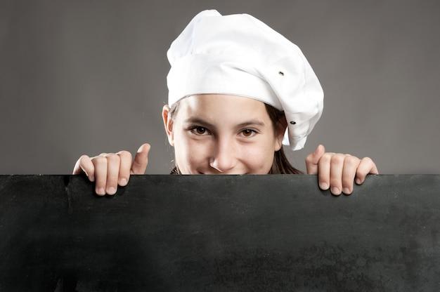 Młody kucharz trzyma tablica menu
