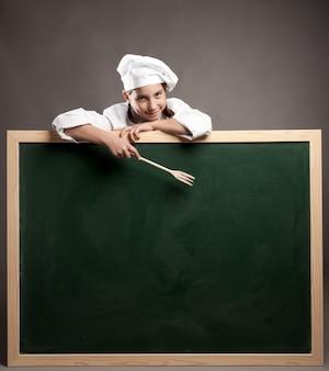 Młody kucharz trzyma zieloną tablicę