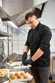 Młody kucharz w czarnej tuniki przygotowuje przekąski gastronomiczne