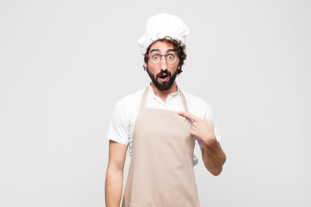 Młody kucharz wyglądający na zszokowanego i zaskoczonego z szeroko otwartymi ustami, wskazując na siebie