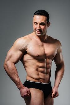 Młody kulturysta-atleta pozuje w studio topless, pokazując swoje mięśnie i brzuch. sport.