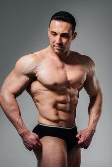 Młody kulturysta-atleta pozuje w studio topless, pokazując swoje mięśnie i brzuch