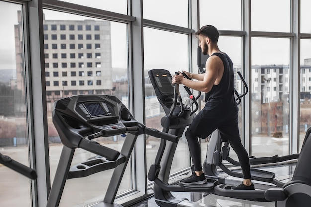 Młody kulturysta prowadzący trening cardio i patrzący przez okno siłowni