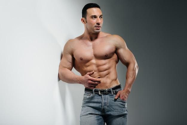 Młody kulturysta sportowiec pozuje w studio topless w dżinsach blisko ściany. sport.