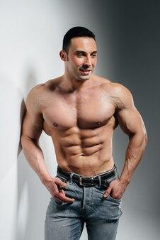 Młody kulturysta sportowiec pozuje w studio topless w dżinsach blisko ściany