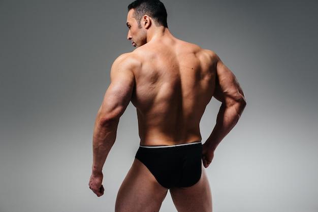 Młody kulturysta sportowiec pozuje w studio topless z powrotem