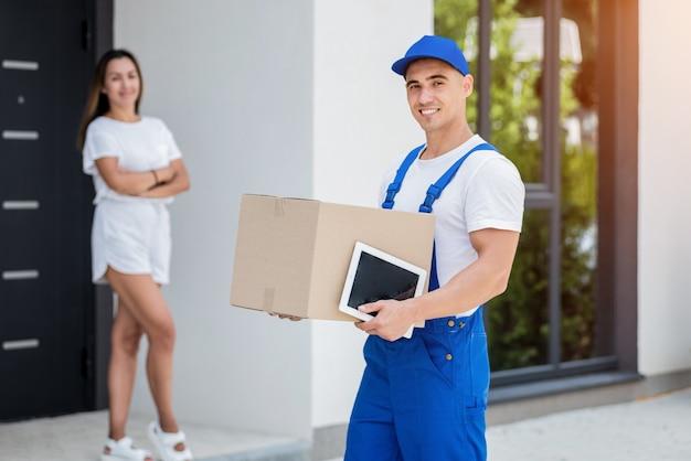 Młody kurier dostarczający towary młodej kobiecie w domu.