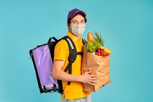 Młody kurier, dostawa mężczyzna w mundurze i masce z plecakiem termicznym i paczką żywności na białym tle. szybka dostawa do domu. zamówienia online podczas pandemii koronawirusa covid-19.