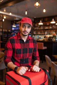 Młody kurier dowozu do kawiarni, stojąc przy dużej czerwonej torbie przed kamerą, idąc dostarczać zamówienia klientów