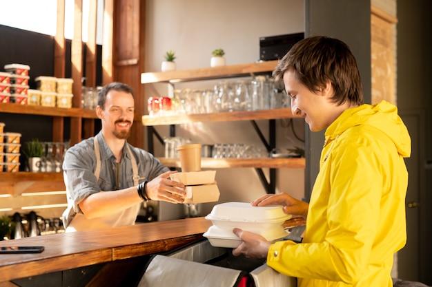Młody kurier trzymający dwa plastikowe pojemniki z gorącą żywnością dla klientów nad otwartym plecakiem podczas pakowania zamówień przy ladzie w kawiarni