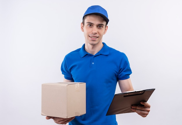 Młody kurier ubrany w niebieski mundur i niebieską czapkę trzyma pudełko i schowek