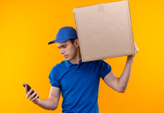 Młody kurier ubrany w niebieski mundur i niebieską czapkę trzyma pudełko trzyma telefon