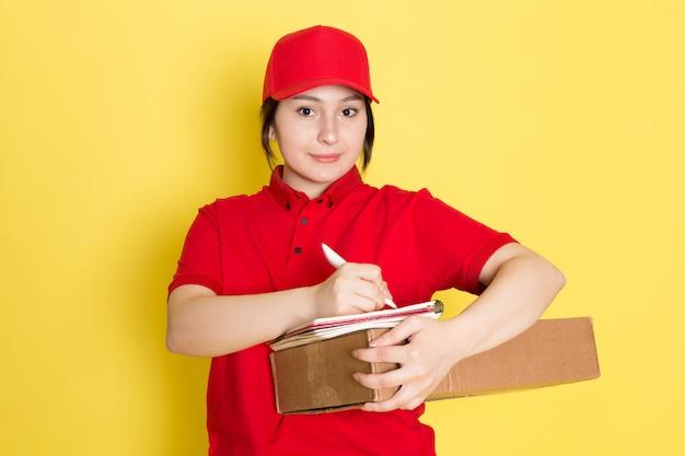Młody kurier w czerwonej polo czerwonej czapce gospodarstwa pakiet zapisywanie notatek uśmiecha się na żółto