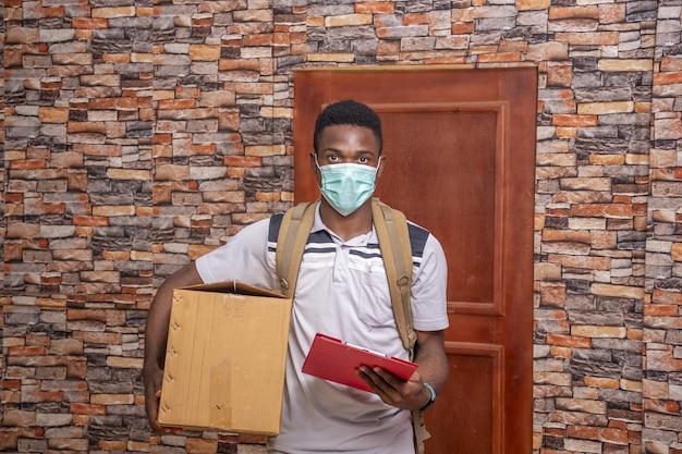 Młody kurier w masce medycznej, trzymający paczkę i dokumenty