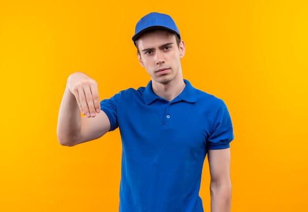 Młody kurier w niebieskim mundurze i niebieskiej czapce robi jego dłoń w dół