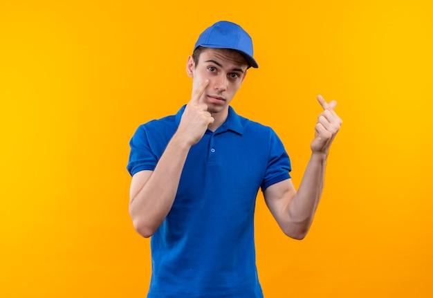 Młody kurier w niebieskim mundurze i niebieskiej czapce robi nieszczęśliwą minę i pokazuje pieniądze palcami
