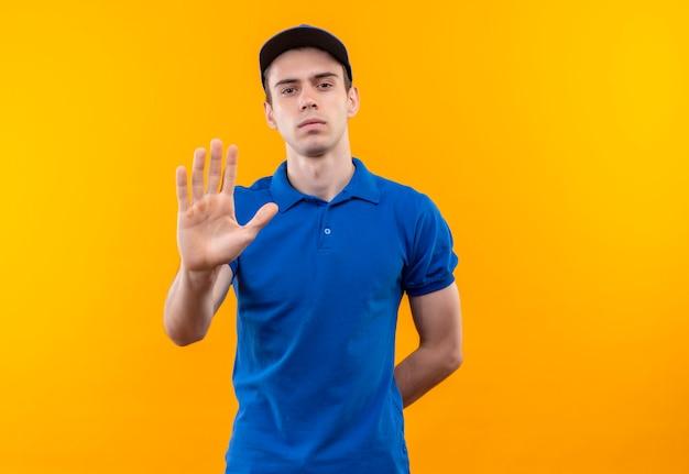 Młody kurier w niebieskim mundurze i niebieskiej czapce robi stop ręką
