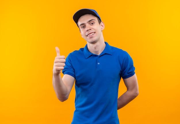 Młody kurier w niebieskim mundurze i niebieskiej czapce robi szczęśliwe kciuki do góry