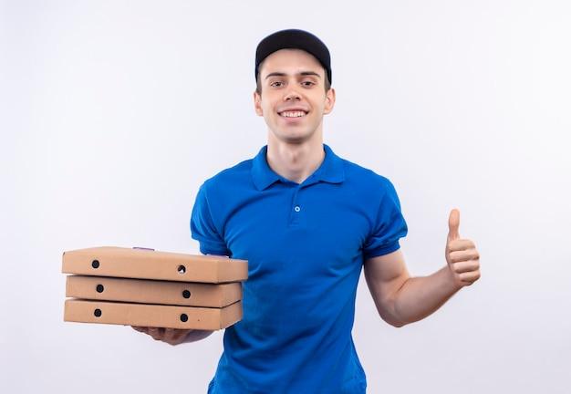 Młody kurier w niebieskim mundurze i niebieskiej czapce robi szczęśliwy kciuk w górę i trzyma pudełka