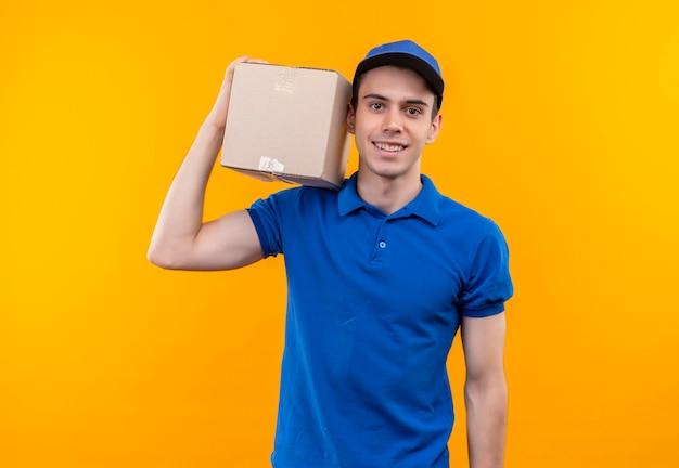 Młody kurier w niebieskim mundurze i niebieskiej czapce szczęśliwie trzyma pudełko na prawym ramieniu