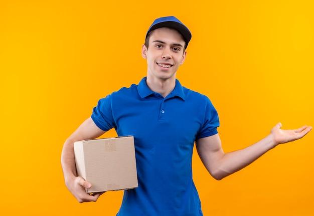 Młody kurier w niebieskim mundurze i niebieskiej czapce szczęśliwie trzyma pudełko
