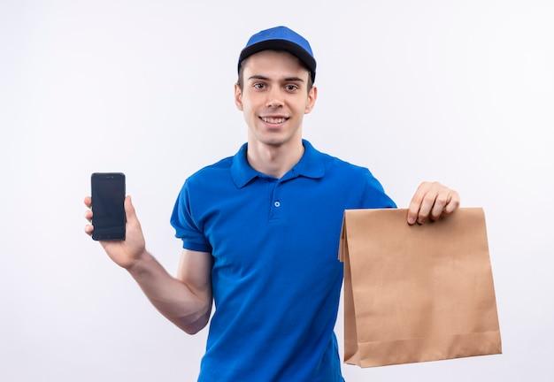 Młody kurier w niebieskim mundurze i niebieskiej czapce szczęśliwie trzyma torbę i telefon