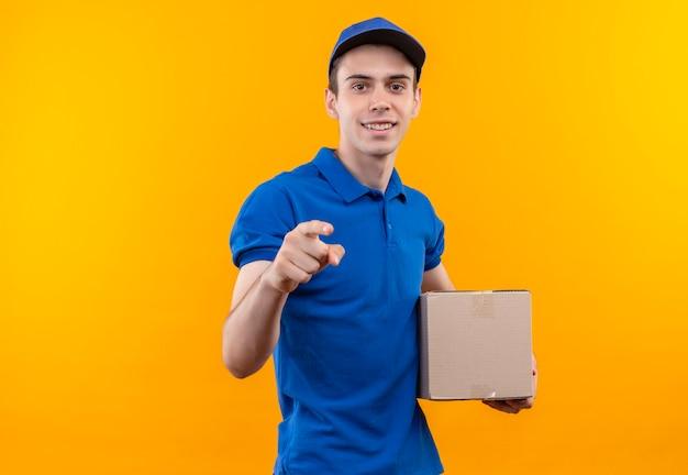 Młody kurier w niebieskim mundurze i niebieskiej czapce szczęśliwie wskazuje i trzyma pudełko