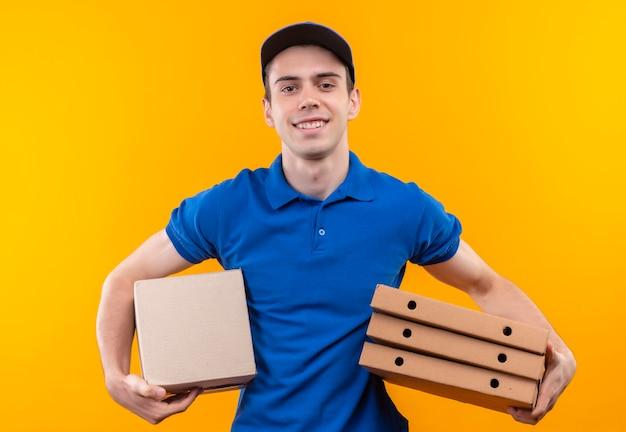 Młody kurier w niebieskim mundurze i niebieskiej czapce trzyma pudełka