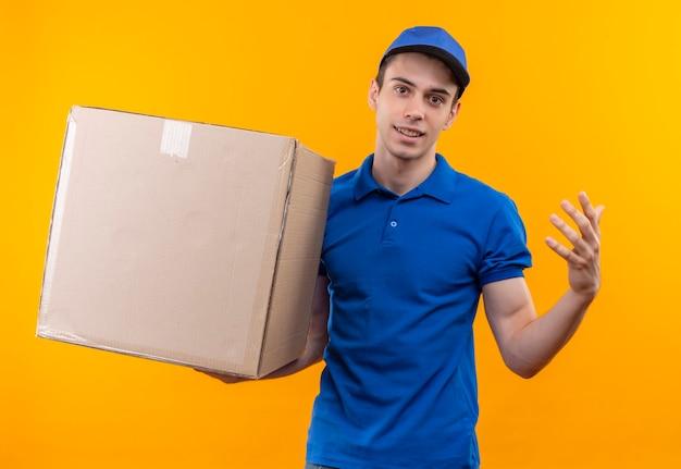Młody kurier w niebieskim mundurze i niebieskiej czapce trzyma pudełko
