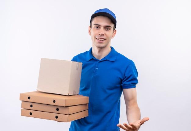 Młody kurier w niebieskim mundurze i niebieskiej czapce uśmiecha się i trzyma pudełka