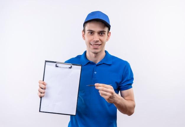 Młody kurier w niebieskim mundurze i niebieskiej czapce uśmiecha się i wskazuje na schowek piórem