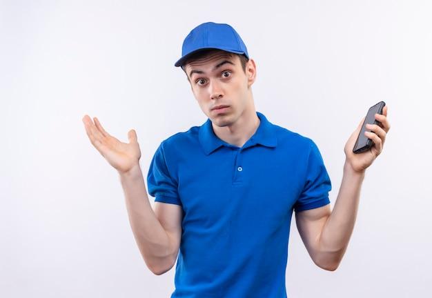 Młody kurier w niebieskim mundurze i niebieskiej czapce zdezorientowany trzyma telefon