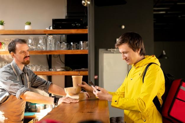 Młody kurier z plecakiem patrząc na adres klienta w smartfonie i sprawdzający kolejność, stojąc przy ladzie przed kelnerem
