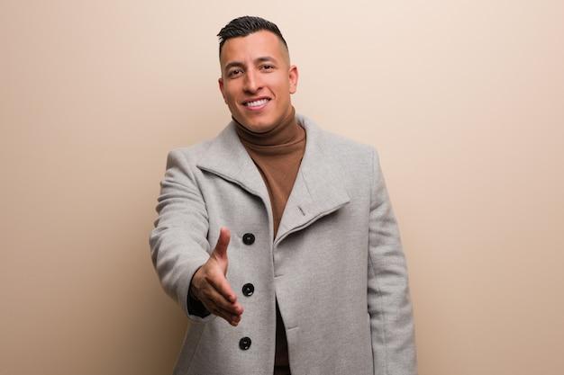 Młody łaciński biznesmen wyciąga rękę, aby kogoś powitać