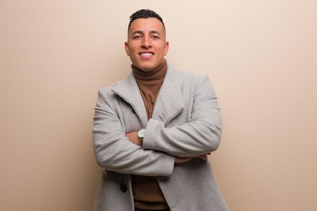 Młody łaciński biznesowy mężczyzna krzyżuje ręki, ono uśmiecha się i relaksujący