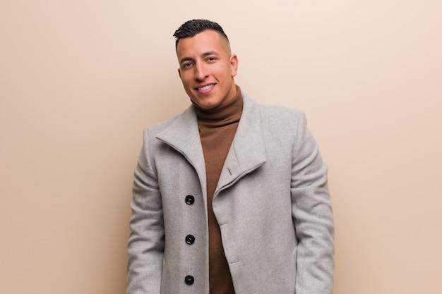 Młody łaciński biznesowy mężczyzna rozochocony z wielkim uśmiechem