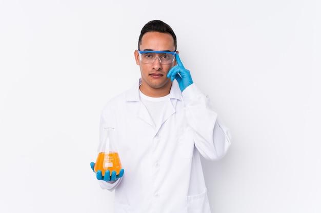Młody łaciński cientific mężczyzna na białym tle wskazując świątynię palcem, myśląc, skupiony na zadaniu.
