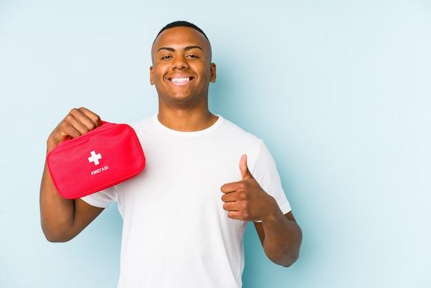 Młody łaciński człowiek robi pierwszą pomoc na białym tle uśmiechając się i podnosząc kciuk do góry