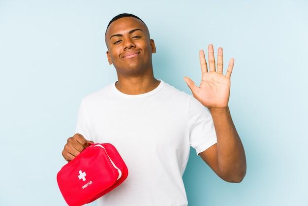 Młody łaciński człowiek robi pierwszą pomoc na białym tle uśmiechnięty wesoły pokazując numer pięć palcami.