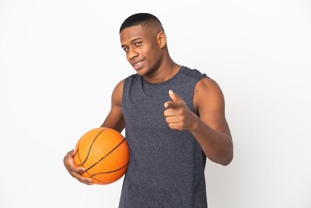 Młody łaciński mężczyzna na białym tle gry w koszykówkę w tylnym położeniu