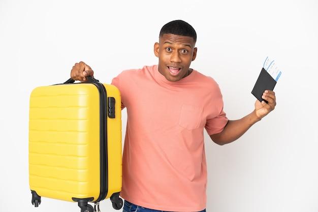 Młody łaciński mężczyzna na białym tle na białej ścianie niezadowolony na wakacjach z walizką i paszportem