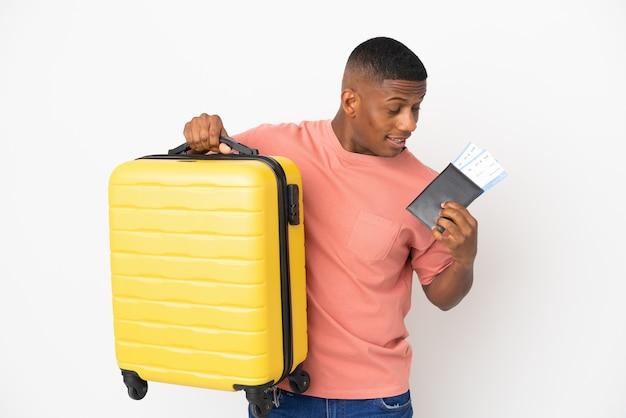 Młody łaciński mężczyzna na białym tle na białej ścianie w wakacje z walizką i paszportem