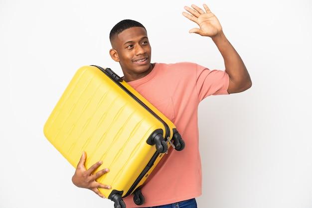 Młody łaciński mężczyzna na białym tle na białej ścianie w wakacje z walizką podróżną i pozdrawiając