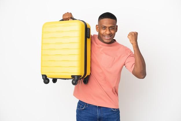 Młody łaciński mężczyzna na białym tle na białej ścianie w wakacje z walizką podróżną