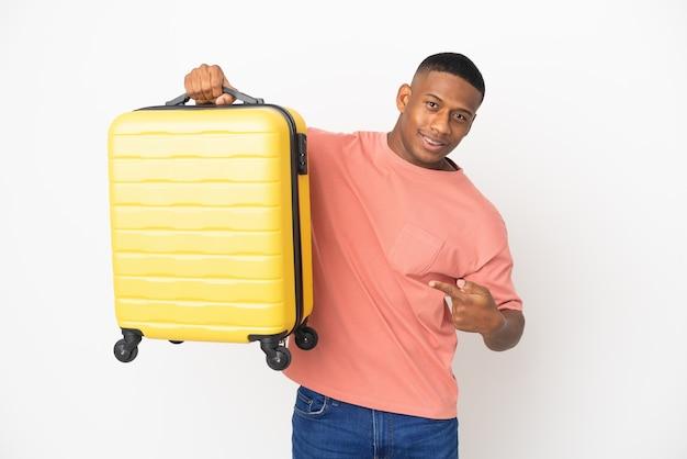 Młody łaciński mężczyzna na białym tle na białym tle w wakacje z walizką podróży