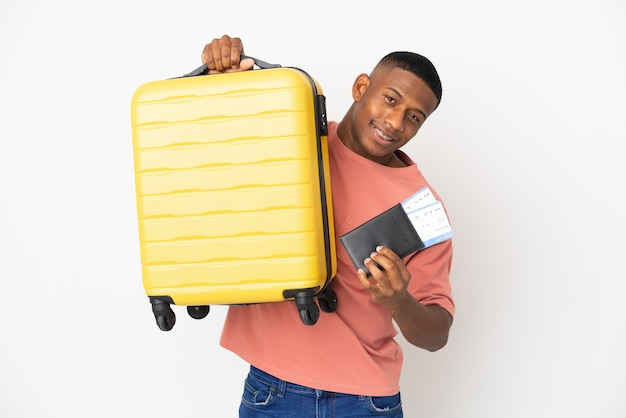 Młody łaciński mężczyzna na białym tle na wakacjach z walizką i paszportem