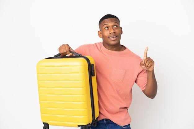 Młody łaciński mężczyzna na białym tle na wakacjach z walizką podróżną i skierowaną w górę