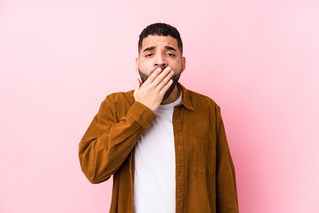 Młody łaciński mężczyzna na różowej ścianie na białym tle ziewanie pokazujący zmęczony gest obejmujący usta ręką.