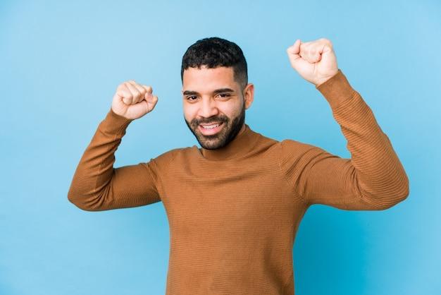 Młody łaciński mężczyzna na tle niebieskiej ściany izolowany świętuje specjalny dzień, podskakuje i energicznie podnosi ręce.